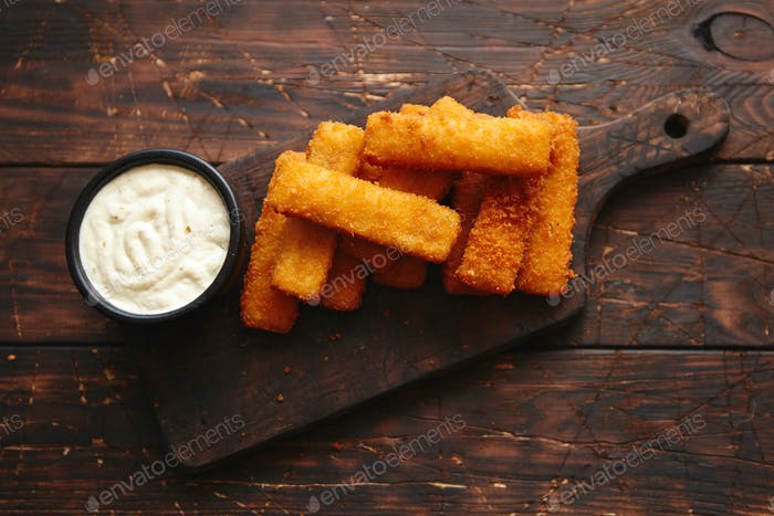 Pile of golden fried fish fingers with white garlic sauce