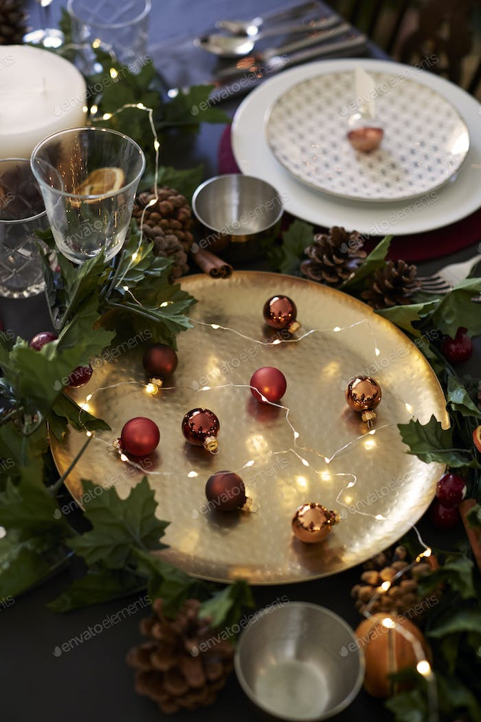 Christmas table setting with baubles on golden plate, bauble name card holder