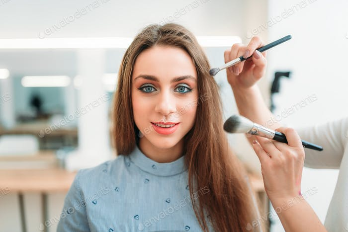 Makeup artist hands with brushes work with woman