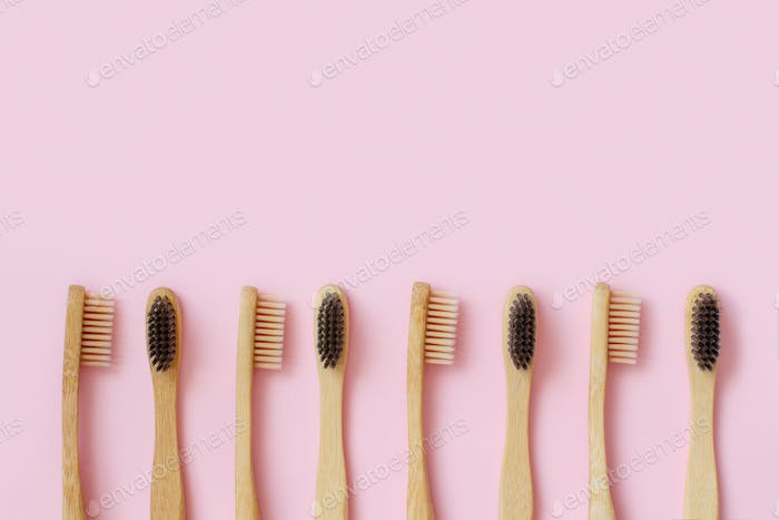 Eco friendly bamboo toothbrushes on pink background