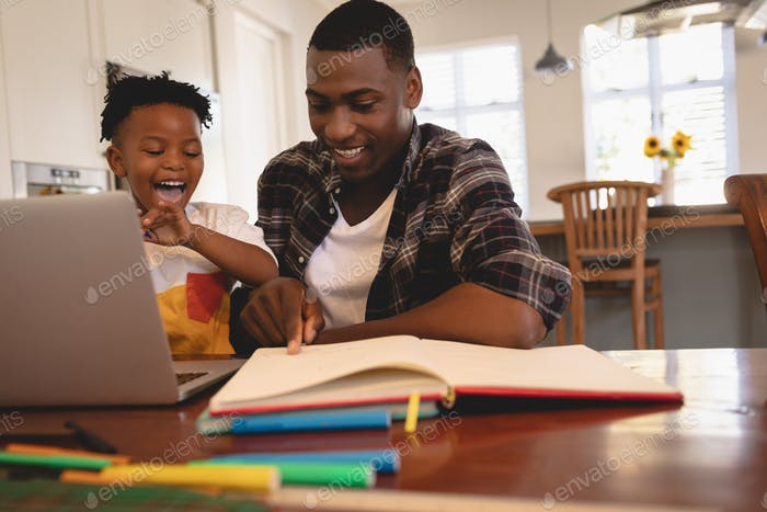 Front view of African American father helping his son with homework with his computer at table