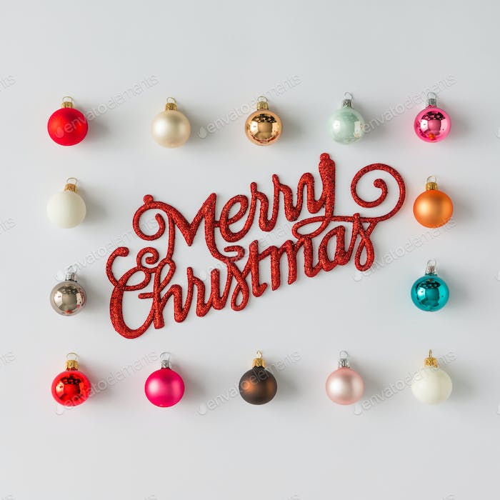 Colorful Christmas baubles decoration with Merry Christmas sign. Flat lay. Holiday concept.