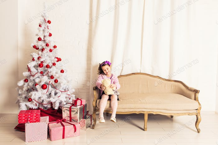 Smiling kid girl holding white teddy bear with christmas tree indoors. Childhood.