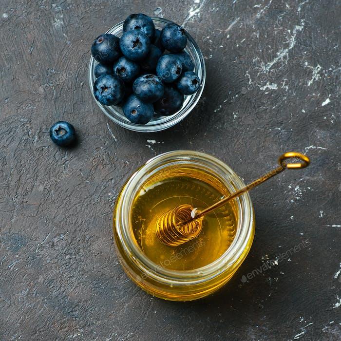 Heidelbeeren und Honig auf dunklem Hintergrund, Draufsicht