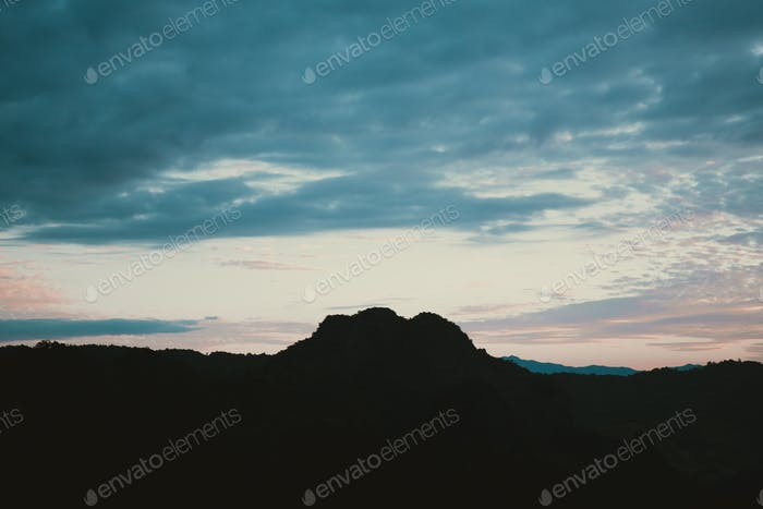 Dramatic sky over mountain silhouette with film process