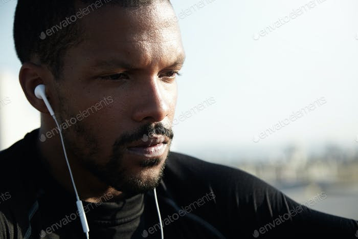 Determined dark-skinned sportsman with beard is listening to music with sad facial expression. Lonel