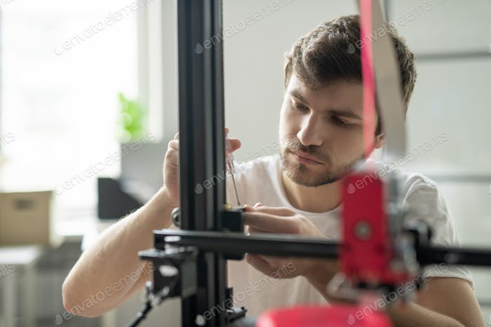 Young businessman standing in front of 3d printer while fixing some details