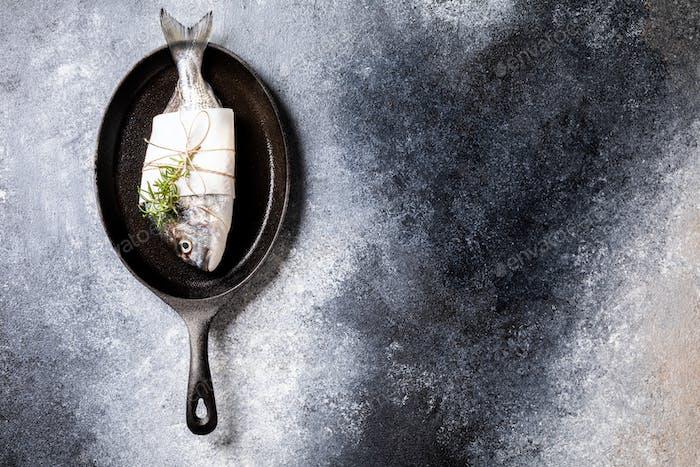 Fresh uncooked Dorado or sea bream fish in the pan