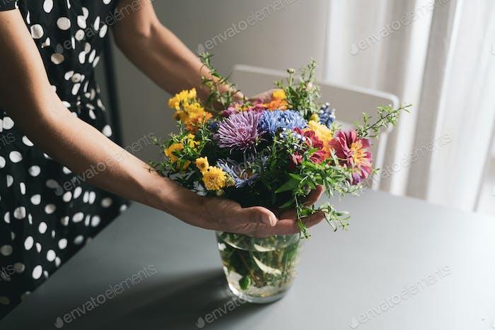 Frau arrangieren einen Blumenstrauß in einer Glasvase