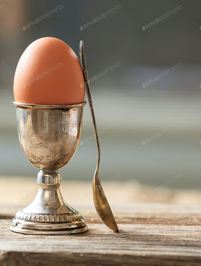 Egg in a silver eggcup and a spoon on wooden table.