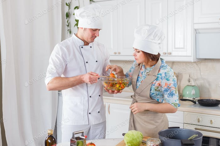 Cook in uniform and his apprentice cooking vegetarian meal