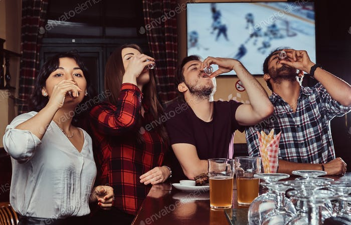 Young multiracial friends drink vodka, resting in the pub.