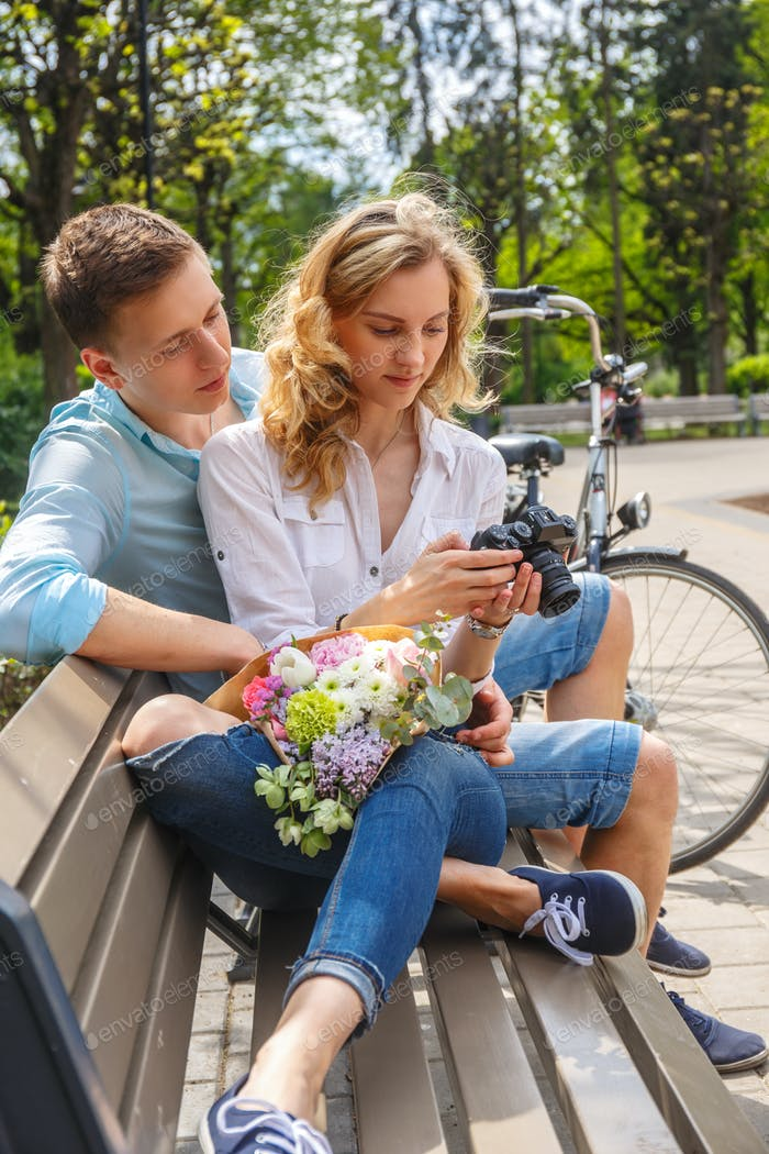 Casual couple using compact dslr photocamera.