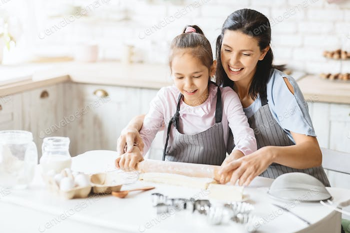 Mother and daughter rolling out the dough for cookies together