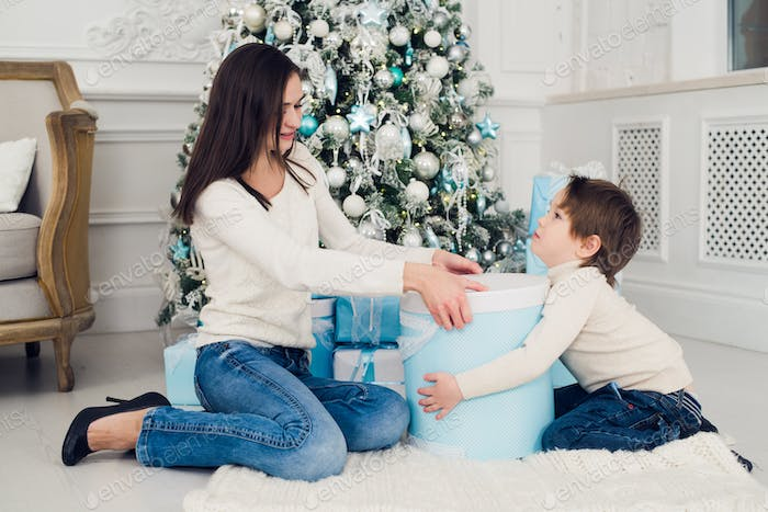 Happy mother with a little boy near Christmas tree. new year gifts