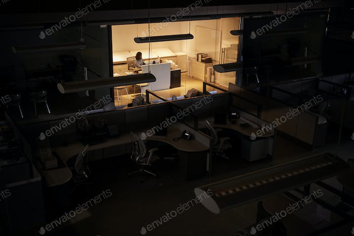 Office worker working late in an otherwise dark office