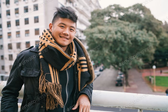Portrait of young Asian man outdoors.