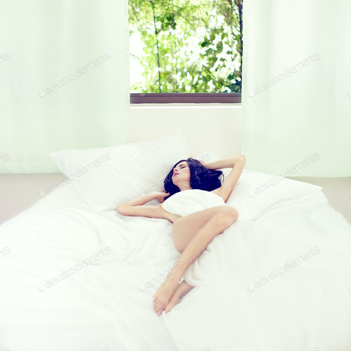 Fashion portrait of a sensual girl in bed