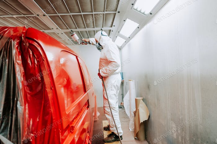 worker painting a red car in a special painting box, wearing a white costume and protection gear