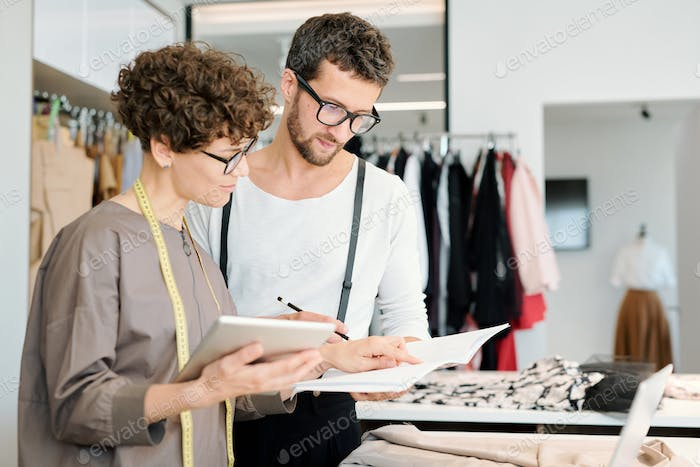 Two young creative fashion designers looking at new sketch