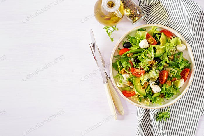Fresh salad with avocado, tomato, olives and mozzarella  in a  bowl