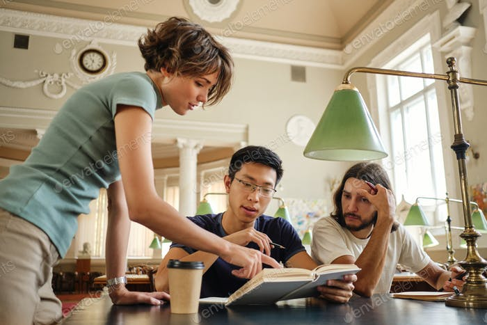 Young tutor helping thoughtful multinational students with study during lesson in university library