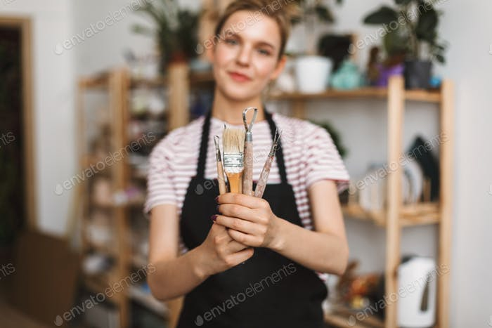 Close up of girl in black apron holding pottery tools in hands spending time at pottery studio