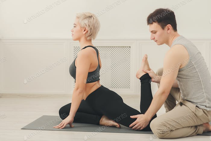 Young woman with yoga instructor in fitness club