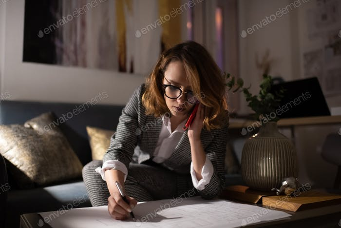 Tired architect making notes of blueprint during call to client