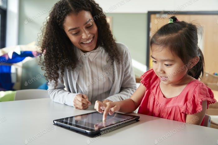 Female infant school teacher working one on one with a Chinese schoolgirl, using tablet