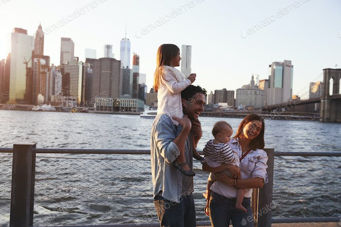 Young family with daughters standing on quayside, side view
