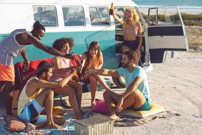 Front view of happy group of diverse friends toasting beer bottle near camper van at beach