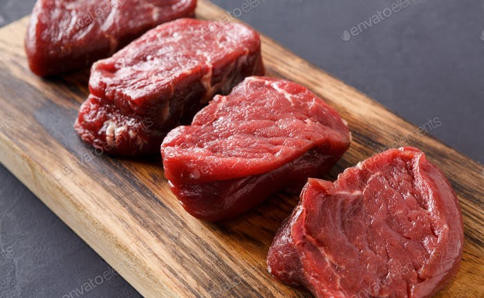 Raw beef filet mignon steaks on wooden board at gray background