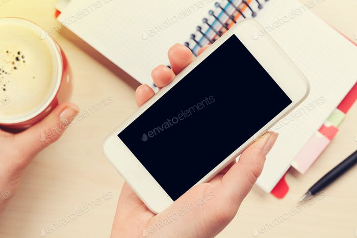 Woman holding smartphone above business desk