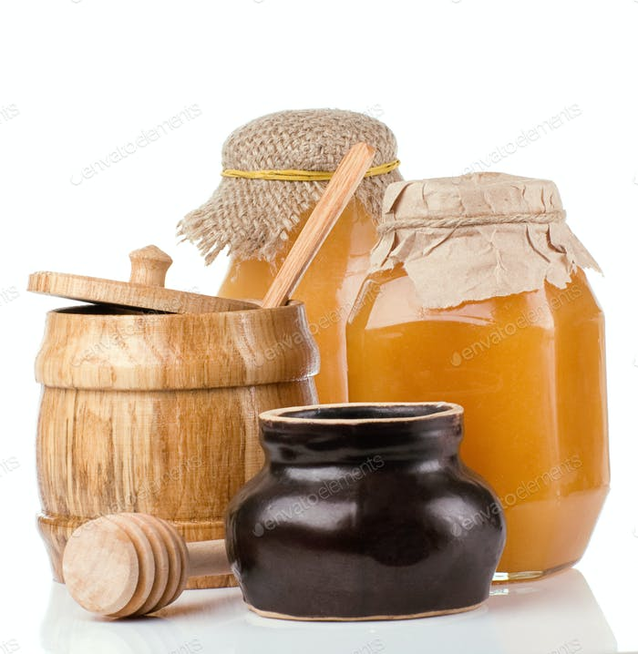 glass, ceramic and wooden jars full of honey