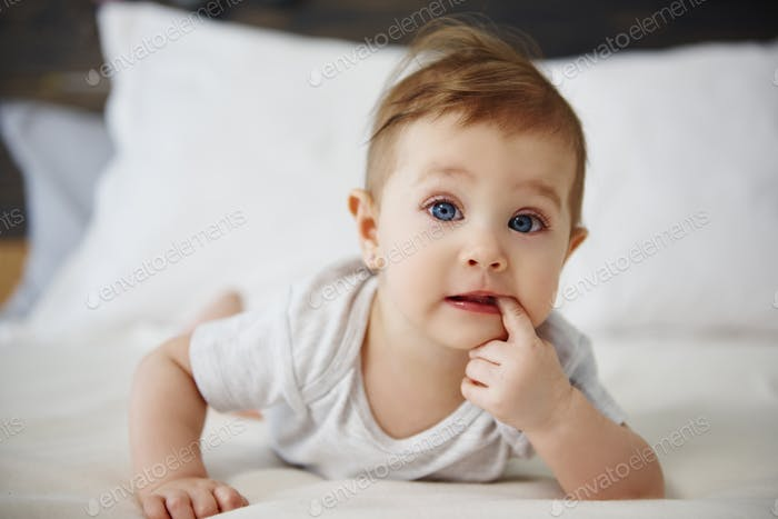 Portrait of confused baby lying on the bed