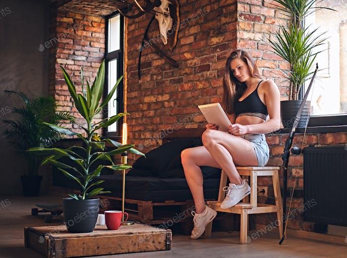 Attraktive sportliche Frau mit Tablet-PC im Loft-Innenraum.