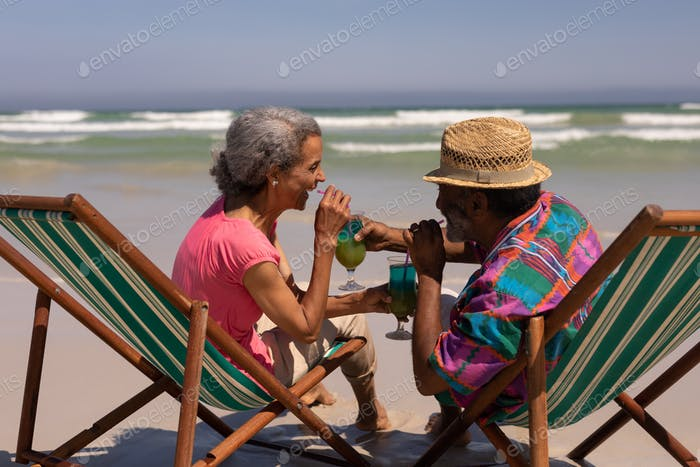 Side view of senior couple relaxing on sun lounger and drinking cocktail on beach in the sunshine