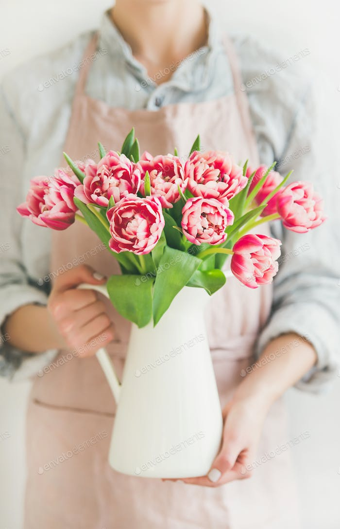 Woman holding white enamel vase with fresh pink tulips