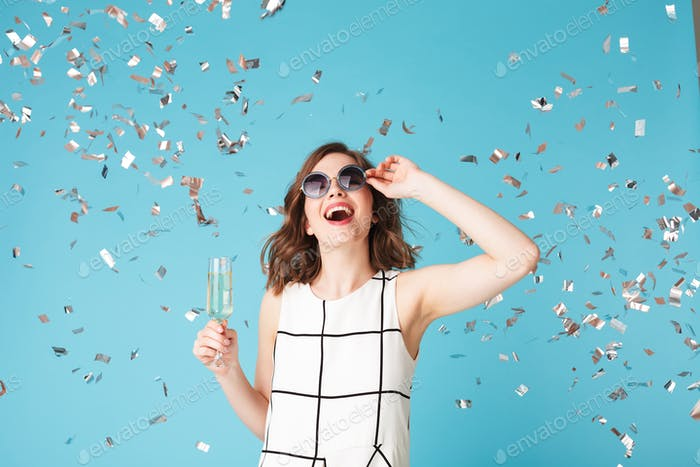 Young happy lady in dress and sunglasses standing with champagne and confetti around on