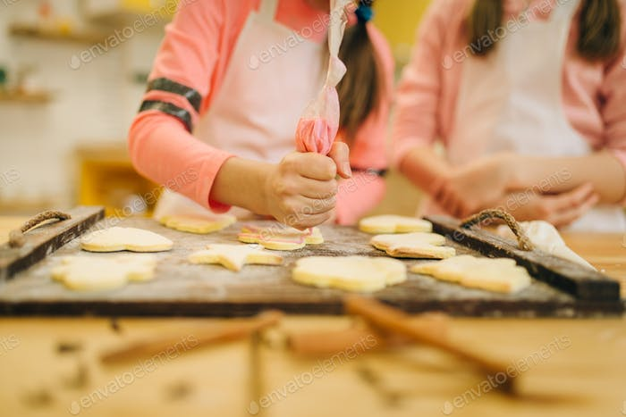 Girls cooks preparing to send cookies in the oven