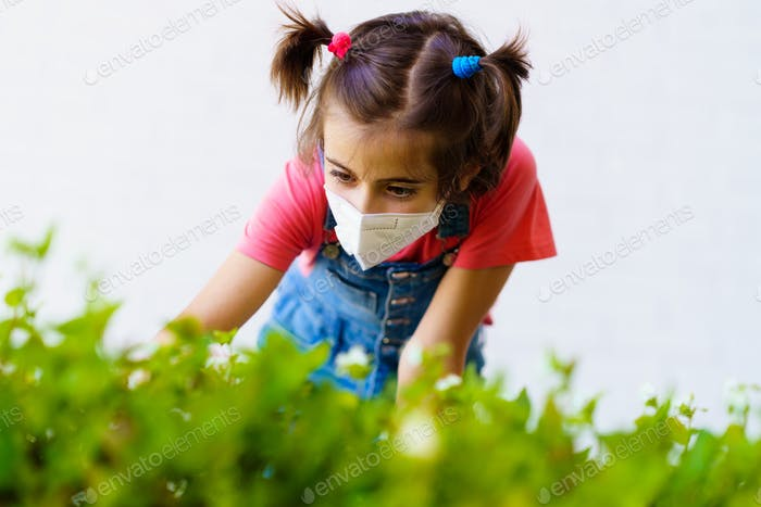 Child girl wearing a protection mask against coronavirus during Covid-19 pandemic