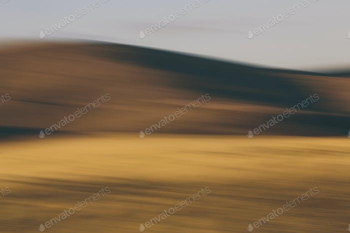 Die Konturen von sanften Hügeln und Ackerland, verschwommene Bewegung und Licht und Schatten.