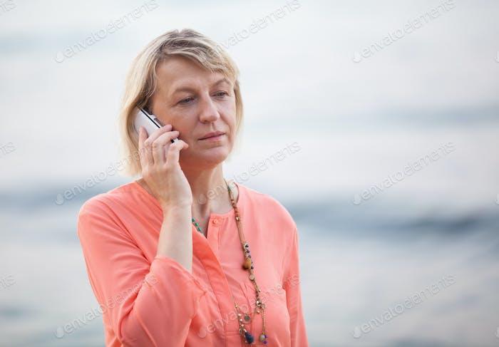 Blond woman having a phone talk outdoor