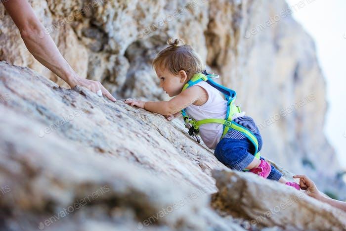 Kleines Mädchen klettern auf Klippe