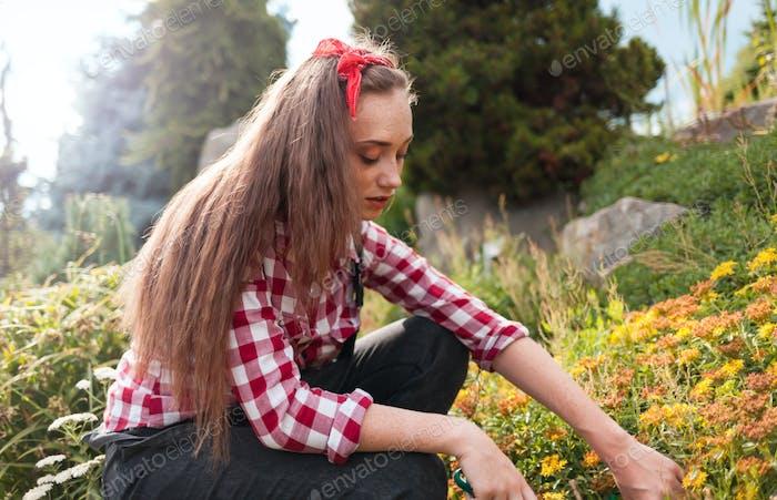 Young woman gardening in her backyard