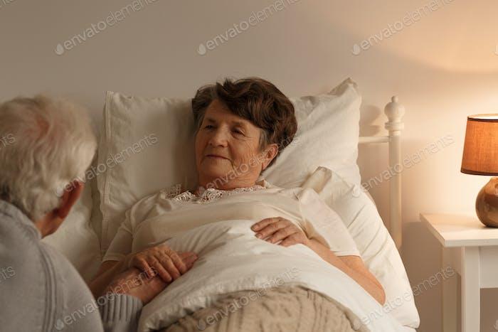 Husband holding sick wife's hand