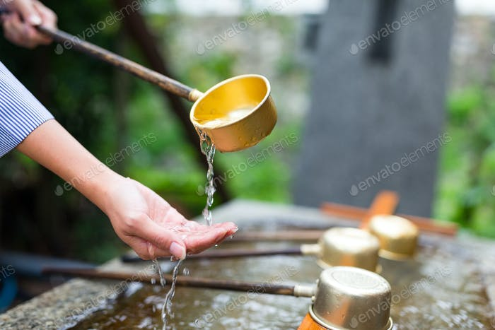 Woman using the water bamboo ladle for purification