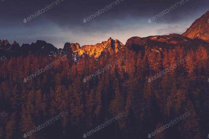 Last sun light hits high mountains peak at sunset