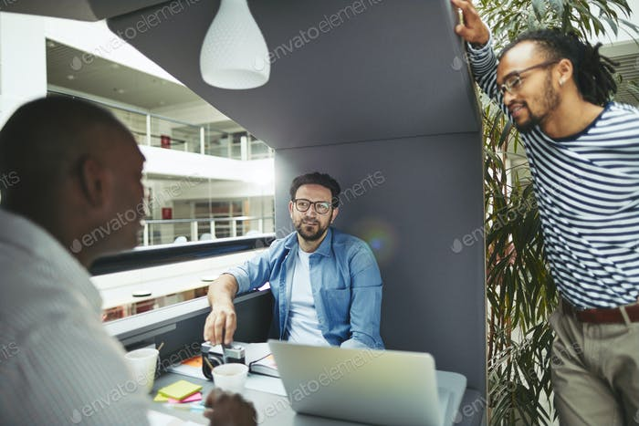 Diverse designers discussing work together in an office meeting pod